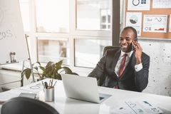Joyful entrepreneur is having pleasant conversation on smartphone. Good news. Cheerful young african businessman is talking with his business partner on mobile Stock Photo