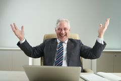 Joyful Entrepreneur with Toothy Smile. Cheerful aged entrepreneur posing for photography with raised hands and toothy smile while celebrating successful project Stock Photos