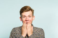 Joyful excited happy man covering mouth emotion. Joyful excited happy smiling man covering mouth with hands. portrait of a young guy on light background. emotion stock image