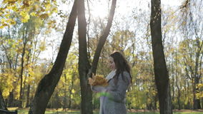Joyful and excited young woman having fun throwing yellow leaves in the sunny fall park. stock footage