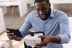 Joyful exited man looking at the virtual reality glasses Stock Photography