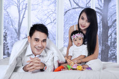 Joyful family on bed in winter day. Portrait of little happy family enjoy winter holiday at home with winter background on the window Royalty Free Stock Photography