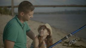 Joyful family catching a fish from shore on river. Joyful relaxed father with cute daughter chatting and fishing on river bank. Active family with fishing rod stock video footage