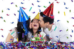 Joyful family celebrating birthday isolated. Attractive family celebrating birthday party while wearing birthday cap and kiss the girl, isolated on white Royalty Free Stock Images
