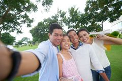 Joyful family. Cheerful Asian family of for taking selfie outdoors after shopping stock photos