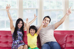 Joyful family expressing happy at home. Portrait of asian family sitting on sofa and expressing happy at home Royalty Free Stock Image