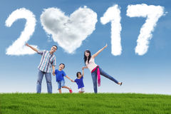Joyful family at field with numbers 2017. Photo of joyful Asian family enjoying holiday on the meadow with cloud shaped numbers 2017 on the sky Stock Photo