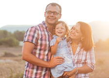 Joyful family. Happy mother, father and daughter in sunset Royalty Free Stock Images