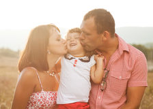 Joyful family. Happy mother, father and daughter in sunset Stock Images