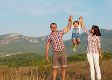 Joyful family. Happy mother, father and daughter in sunset Royalty Free Stock Photo