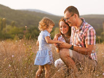 Joyful family. Happy mother, father and daughter in sunset Stock Image