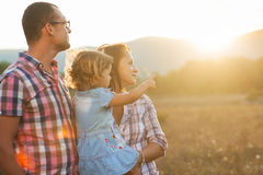 Joyful family. Happy mother, father and daughter in sunset Royalty Free Stock Photography