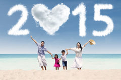 Joyful family having fun in vacation. Cheerful family holding hands and run together at the beach in new year holiday Stock Photos