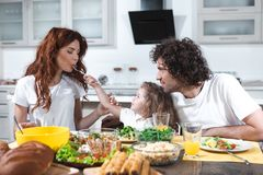 Joyful family having lunch together at home stock image