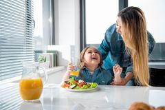 Joyful family having together in kitchen. My little baby. Happy asian women is expressing tenderness to her daughter while standing in kitchen. Girl is drinking Stock Images