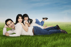 Joyful family lying on grass at the park. Portrait of happy family smiling at the camera while relaxing and lying on the grass at field Royalty Free Stock Photo