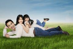 Joyful family lying on grass at the park Royalty Free Stock Photo