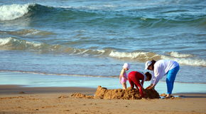 Joyful family, mother with two daughters building sandcastle on the beach Royalty Free Stock Photography