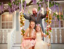 Joyful family parents with daughter at home in blooming garden on swing stock images