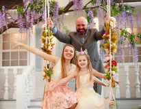Joyful family parents with daughter at home in blooming garden on swing royalty free stock image