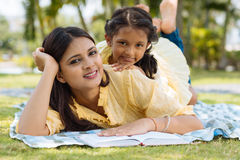 Joyful family in the park. Joyful Indian mother and daughter lying on grass in the park Royalty Free Stock Images