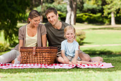 Joyful family picnicking in the park. With a slick Royalty Free Stock Photos