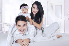Joyful family playing in the bedroom. Beautiful asian family playing together in the bedroom, looking at camera Royalty Free Stock Photo