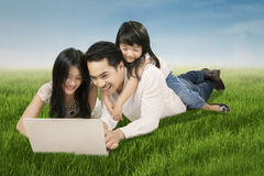 Joyful family playing laptop at field Royalty Free Stock Photo