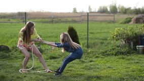 Joyful family playing tug of war in yard outdoors. Charming young blonde mother and her cute daughter having fun outdoors, playing tug of war in the yard during stock video