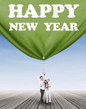 Joyful family pulling a banner new year Royalty Free Stock Photo
