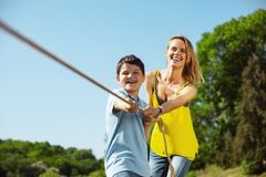 Joyful family pulling a rope in the park. Outdoor activities. Alert loving mother helping her son while he pulling a rope with his sister Royalty Free Stock Images