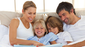Joyful family reading a book on bed. With mother showing a page royalty free stock image