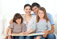 Joyful family reading together on the sofa Stock Photography