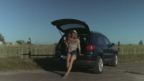 Joyful family relaxing on summer vacation roadtrip. Cute little girl embracing her beautiful mother busy with smart phone in stylish outfit while sitting in car stock footage