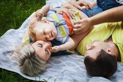 Joyful family resting in park Stock Photos