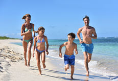 Joyful family running on the beach Stock Image