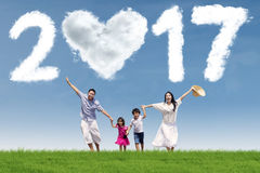 Joyful family running on meadow with 2017. Photo of joyful Asian family running on the meadow while holding hands together with cloud shaped numbers 2017 Royalty Free Stock Photos