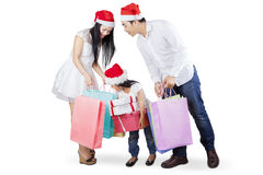 Joyful family with shopping bags. Asian family wearing santa hat and looking at shopping bag, isolated over white background Royalty Free Stock Photos