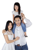 Joyful family smiling at camera in studio. Cheerful family standing in studio while smiling at camera, isolated over white Stock Images