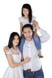Joyful family smiling at camera in studio Stock Images