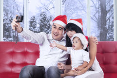 Joyful family taking picture together. Young asian family wearing santa hat and using a digital camera to take self portrait at home Stock Photography