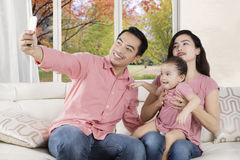 Joyful family taking selfie photo. Picture of joyful Asian family sitting on the couch while taking selfie portrait with a mobile phone Stock Image