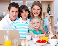 Joyful family using laptop during the breakfast Stock Photography
