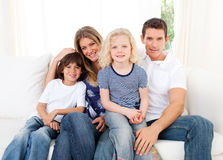 Joyful family watching television sitting on sofa. At home Royalty Free Stock Image