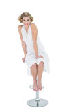 Joyful fashion blonde model sitting on bar chair Royalty Free Stock Image