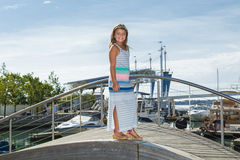 Joyful  fashionable little girl standing on wooden hill in downtown Toronto near waterfront Stock Photography