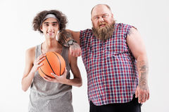 Joyful fat hipster and thin outcast are friends. Together we are strength. Portrait of confident thick bearded men leaning on shoulder of slim boy friendly. Weak Royalty Free Stock Photo