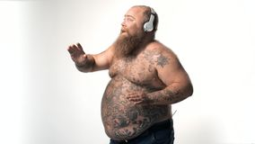 Joyful fat man listening song and dancing. Happy male is enjoying music and moving in rhythm with pleasure. He is wearing headphones and laughing. He has large