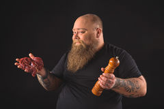 Joyful fat man is ready to prepare dinner. Lets cook something delicious. Portrait of excited thick guy showing meat and pepper tool. He is looking at camera and royalty free stock image