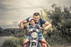 Joyful father biker son riding motorcycle lifestyle portrait concept happy paternity. And father`s day royalty free stock image